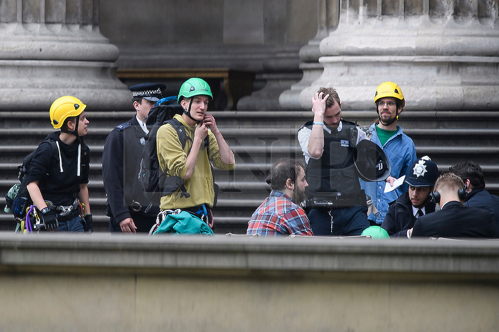 © Licensed to London News Pictures. 19/05/2016. London, UK. Climbers who scaled the building being questioned by police. A Greenpeace protest by Greenpeace at the British museum which has closed the museum. Greenpeace climbers have scaled pillars at the museum, erecting banners protesting against BP sponsorship of Sunken Cities: Egypts - Lost Worlds exhibition at the museum. Photo credit: Ben Cawthra/LNP