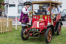 Datchet, UK. 30 June, 2019. Chris Brown, Official Town Crier of the Royal Borough of Windsor and Maidenhead, welcomes the driver of a 1904 De Dion Bouton, the first of many pre-1905 vehicles to arrive on the 48-mile Ellis Journey from Micheldever station near Winchester to Datchet, a reenactment of the first recorded journey by a motorised carriage in England undertaken by pioneer automobilist Hon. Evelyn Ellis in his new, custom-built Panhard-Levassor on 5th July 1895.
