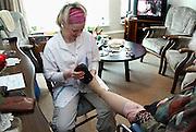 Nederland, Nijmegen, 30-3-2006..Een verpleegkundige van de thuiszorg doet haar ronde en helpt een oudere vrouw, die nog zelfstandig woont, met haar schoenen...Foto: Flip Franssen