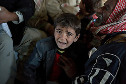 © Licensed to London News Pictures. 11/12/2014. Sinjar Mountains, Iraq. A young Yazidi refugee cries after running a gauntlet of older and stronger refugees who pushed their way onto an Iraqi Air Force Mi-17 Hip helicopter that will evacuate he and his family.<br /> <br /> Although a well publicised exodus of Yazidi refugees took place from Mount Sinjar in August 2014 many still remain on top of the 75 km long ridge-line, with estimates varying from 2000-8000 people, after a corridor kept open by Syrian-Kurdish YPG fighters collapsed during an Islamic State offensive. The mountain is now surrounded on all sides with winter closing in, the only chance of escape or supply being by Iraqi Air Force helicopters. Photo credit: Matt Cetti-Roberts/LNP
