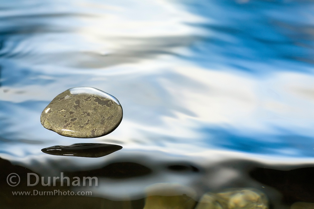 A rock just about to hit the water's surface.