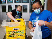 22 APRIL 2020 - DES MOINES, IOWA: SIMONA LEWIS (right) and KALY WOLFE pack milk into grab and go lunches at Edmunds Elementary School. Schools in Iowa are closed for the rest of the school year because of the COVID-19 (Coronavirus/SAR-CoV-2) pandemic. Des Moines Public Schools expanded their school lunch and distance learning efforts this week. Lunches are being distributed at all of the district's elementary and middle schools and officials have started distributing computers so students can participate in distance learning. The meal distribution was done according to social distancing guidelines.          PHOTO BY JACK KURTZ