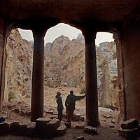 Travelers admire pillars in one of huge, carved buildings in Jordan's mysterious Petra, a World Heritage Site.