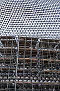 Modern landmark architecture of the Selfridges Building covered in scaffolding while it is being renovated on 7th January 2021 in Birmingham, United Kingdom. The building is part of the Bullring Shopping Centre and houses Selfridges Department Store. The building was completed in 2003 at a cost of £60 million and designed by architecture firm Future Systems. It has a steel framework with sprayed concrete facade. Since its construction, the building has become an iconic architectural landmark and seen as a major contribution to the regeneration of Birmingham.