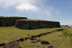 Chile, Easter Island: Orongo Village, restored archeological site where the birdman cult was practiced.  The birdman cult decided king-of-year governance by requiring athletes to bring the first egg of the season from offshore islands.  The athlete's patron became king.  The site has stone houses, petroglyphs, and a crater lake where the athletes cut reeds to make rafts to get to the island..Photo #: ch274-33727.Photo copyright Lee Foster www.fostertravel.com lee@fostertravel.com 510-549-2202