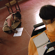 A girl is doing her class assignments on the floor as a friend passes by on her wheel chair at APD School in Bangalore
