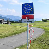 18.05.2020, Grenzübergang, Sulzberg (Vorarlberg), AUT, Coronavirus, Erleichterungen an der Grenze von Bayern nach Vorarlberg und Tirol, seit 13.05.2020 können Land- und Forstwirte von 7-20 Uhr weitere Grenzübergänge nutzen. Ein Landwirt bewirtschaftet eine Wiese. Ein Teil der Wiese befindet sich in Bayern, der andere Teil in Vorarlberg.<br /> im Bild Schilder kennzeichnen die Staatsgrenze, ein Absperrband flattert im Wind<br /> <br /> Foto © nordphoto / Hafner