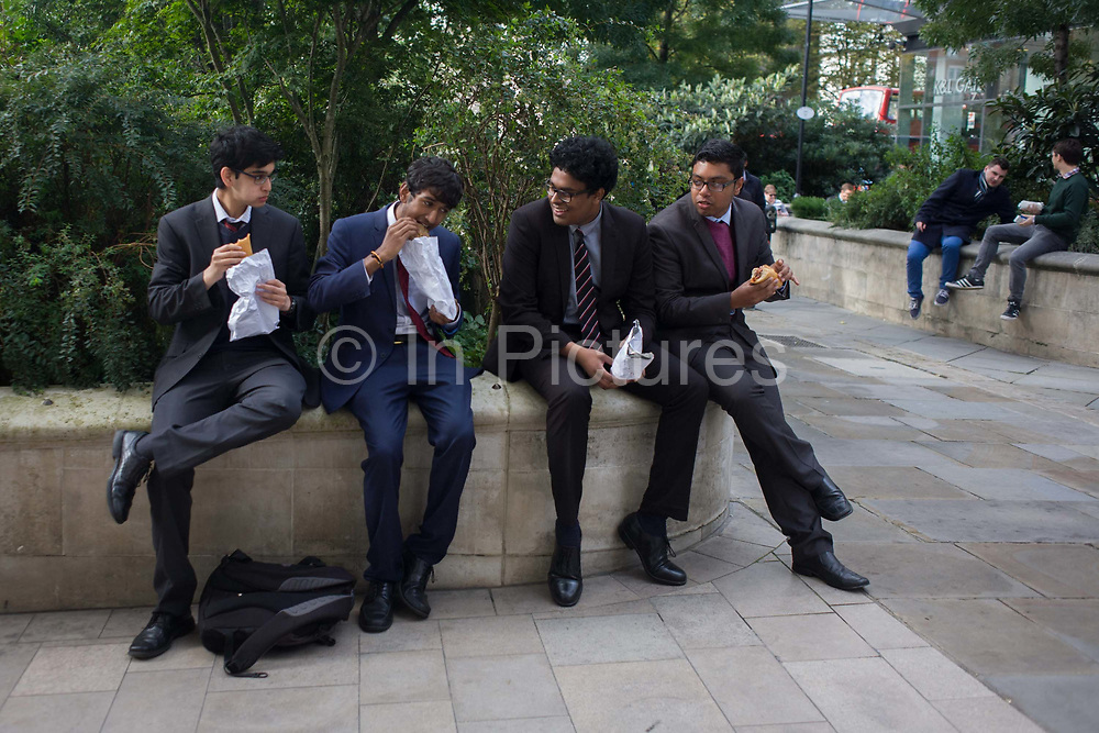 Four men of Asian appearance share a funny moment while eating lunch in a City of London park. Sat on a park corner wall near St Paul's cathedral, the 4 munch and bite their sandwiches and pies bought nearby. One has shared a humerous moment and the others react at the apparent joke. The small green space is located in the City of London, the capital's financial financial heart and historic centre founded by the Romans in AD43 but now the point of focus for Britain's economy.