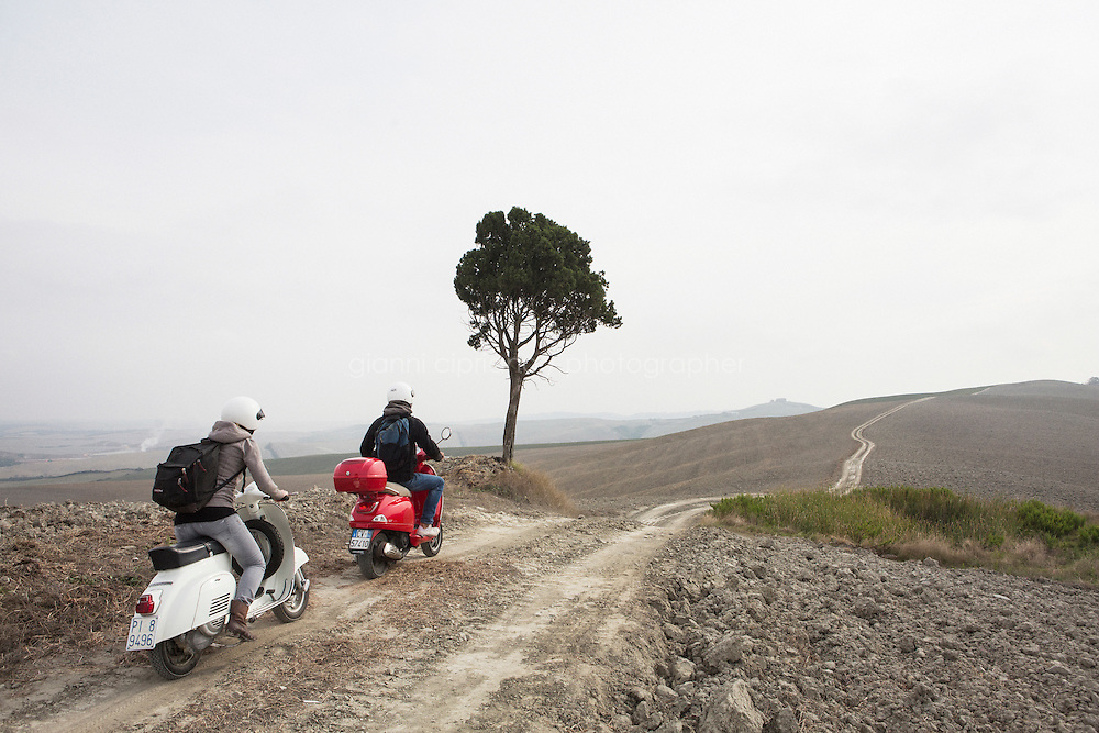 Asciano, Italy - 10 September 2014: Journalist Tina Nachtmann rides a Vespa 125 Primavera of 1974 on a road trip through Tuscany with her travel companion Michele, through the Crete Senesi in Asciano, Italy, on September 10th 2014.<br /> <br /> The Crete Senesi refers to an area of the Italian region of Tuscany to the south of Siena. It consists of a range of hills and woods among villages and includes the comuni of Asciano, Buonconvento, Monteroni d'Arbia, Rapolano Terme and San Giovanni d'Asso, all within the province of Siena. Crete senesi are literally 'Senese clays', and the distinctive grey colouration of the soil gives the landscape an appearance often described as lunar.