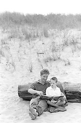 father and son reading while sitting on the beach in East Hampton, NY
