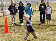 First grader Adam Kotzian (C) takes his turn to run a lap as is watched by his classmates during physical education class at Eagleview Elementary school in Thornton, Colorado March 31, 2010.  Adam and his parents are achondroplasia dwarfs but his sister Avery is not.   REUTERS/Rick Wilking (UNITED STATES)