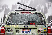 SHOT 3/15/16 9:49:28 AM - A Ford Escape covered with ski stickers and a Skibum1 license plate parked in the lot at Alta ski area. Alta is a ski area in the western United States, located in the town of Alta in the Wasatch Mountains of Utah, in Salt Lake County. With a skiable area of 2,200 acres, Alta's base elevation is 8,530 ft and rises to 10,550 ft for a vertical gain of 2,020 ft. One of the oldest ski resorts in the country, it opened its first lift in early 1939. Alta is known for being very high altitude and receives more snow than most Utah resorts, its average annual snowfall is 514 inches. Alta is one of three remaining ski resorts in America that prohibits snowboarders. (Photo by Marc Piscotty / © 2016)