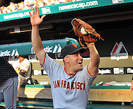 Omar Vizquel raises his arms while watching himself hit a home run during a tribute video before his first game back in Cleveland.