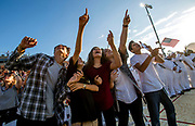 Moses Monsoor, 17, Vincent Monsoor, 12, Isabella Monsoor, 13, Laney Fernandez, 16, and Samuel Monsoor, 14, from left, watch a parachute tribute by the Patriot Parachute Team during the Michael A. Monsoor Memorial Stadium dedication at Garden Grove High School in Garden Grove, CA. The stadium was dedicated to their uncle, a US Navy SEAL who was killed when he threw himself onto a grenade to protect his fellow SEAL team members in Iraq in 2006.