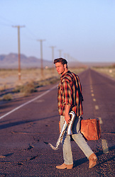 man walking on an empty road with a suitcase and saxophone