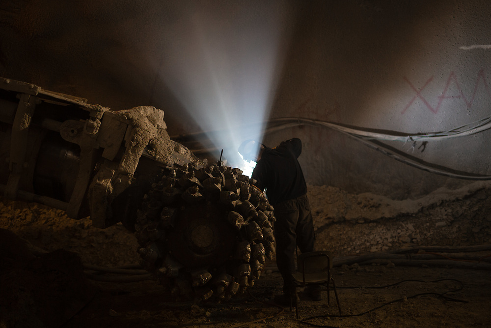 A worker welds as he performs maintenance work on a drill head of a tunneling machine at the construction site of an underground tunnel designated for traditional Jewish burial at the Givat Shaul cemetery, in Jerusalem, Israel, on May 14, 2015.