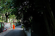 A Buddhist monk walks down an alley in Chiang Mai, Thailand.