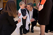 A father reassures and congratulates his 4 year-old son after his baptism ceremony in a local Catholic church.