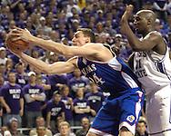 Kansas center Sasha Kaun (C) reaches for a rebound against pressure from Kansas State's Dramane Diarra (R), during the second half at Bramlage Coliseum in Manhattan, Kansas, March 4, 2006.  The Jayhawks won 66-52.