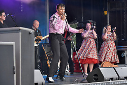"""© Licensed to London News Pictures. 23/07/2017. London, UK. Michael Glaysher on stage as a young Elvis.  Fans attend the capital's first ever """"Elvis Fest"""" to mark the 40th anniversary of the King of Rock N' Roll's death.  Taking place in Parsloes Park, Dagenham, the festival includes a variety of tribute acts representing Elvis through his career. Photo credit : Stephen Chung/LNP"""