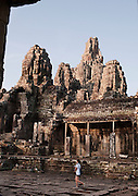 A tourist visitor walks through the Bayon temple at Angkor, Siem Reap Province, Cambodia