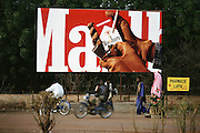 Villagers pass in front of Marlboro billboard on the main road  in the W. African town of San, Mali during market day. Material World Project.