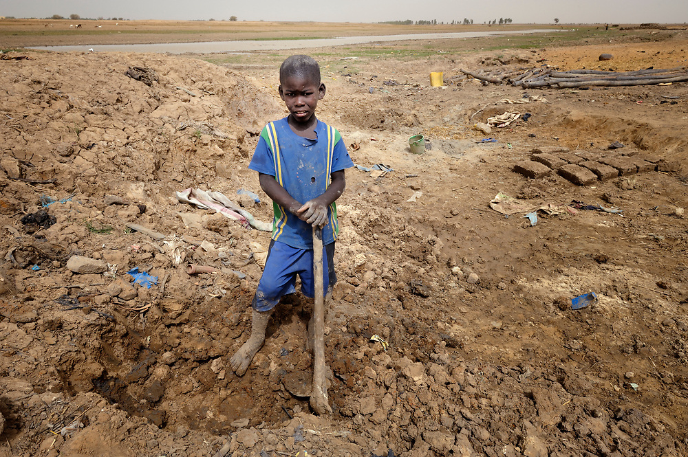 Mohamed Ag Aldjoumett, age 10, pauses from digging clay to make bricks for his family's home in Toya, a village in northern Mali near Timbuktu. The region was seized by Islamist fighters in 2012 and then liberated by French and Malian soldiers in early 2013. The Sahel region has been affected by a food crisis for years, often exacerbated by severe droughts.