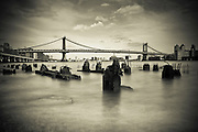 Black and white sepia long exposure photography of the Manhattan bridge taken from Downtown Manhattan in New york