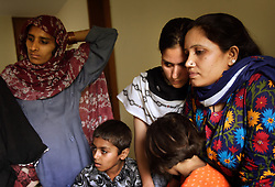 Shebana, 22, second from right, watches a sewing lesson with a friend at Dastak, a shelter opened in 1990 for abused women seeking refuge by the AGHA Legal Aid Cell, Lahore, Pakistan, May 2, 2003. Shebana resides at the shelter because her parents disapproved of her wanting to have a love marriage. The boyfriend brought her to the shelter for protection and was later killed by her parents.
