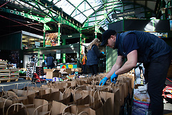 EDITORIAL USE ONLY Volunteers prepare some of the thousand fruit and vegetable packages destined for healthcare workers fighting the COVID-19 pandemic as Borough Market spearheads the national 'Feed The Frontline' campaign, London.