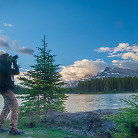 A photographer shoots beside in early morning light by Two Jack Lake in Banff National Park, Alberta, Canada.  Behind is Mount Rundle.
