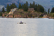 A Fisherman rowing his boat on Okanagan Lake near Ellison Provincial Park in Vernon, British Columbia, Canada