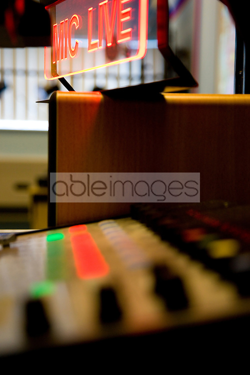 Close up of a mixing board and illuminated sign in a radio station