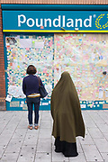 Local Peckham shoppers stop to read the spontaneous messages of love on the Poundland peace wall after the London riots. In response to the violence and destruction that took place the week before, communities reacted with anger in a way rarely seen in a large UK city these days. The messages vary in their sentiment but generally echo a sense of disgust at the looting and rioting with brief notes of co-operation, advice and communal encouragement. Walls like these have sprung up in other locations where destruction was widespread and locals lost their convenience stores, sports shops and even homes.