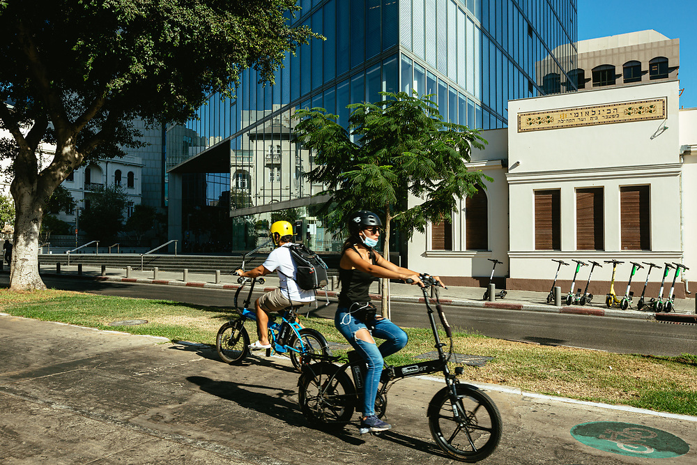 Cyclists are seen driving along Sderot Rothschild (Rothschild Boulevard), a mostly a tree-lined boulevard with lanes for pedestrians and cyclists, playgrounds for children, coffee shops and kiosks in central Tel Aviv, Israel, on August 19, 2020.