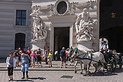 Dominated by giant Romanesque figures depicting Hercules slaying Hydra, elderly tourists and a fiaker horse-drawn carriage vie for cobbled space outside St. Michaels Church on Michaelerplatz, on 28th June 2016 in Vienna, Austria. St. Michaels is one of the oldest churches in Vienna.