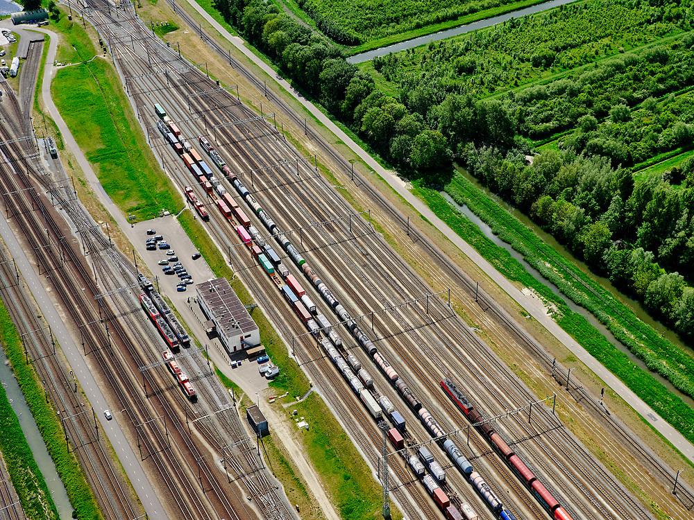 Nederland, Zuid-Holland, Zwijndrecht, 14-05-2020; Kijfhoek, rangeerterrein voor goederentreinen. Overzicht van de verdeelsporen (richting Dordrecht). Kijfhoek huisvest Keyrail, exploitant Betuweroute en is in beheer bij ProRail. De Betuweroute, die begint als Havenspoorlijn op de Maasvlakte, verbindt via Kijfhoek de Rotterdamse haven met het achterland. Het rangeeremplacement dient voor het sorteren van goederenwagons waarbij gebruik gemaakt wordt van de zwaartekracht, het 'heuvelen': de wagons worden de heuvel opgeduwd, bij het de heuvel afrollen komen ze, door middel van wissels, op verschillende verdeelsporen. Railremmen zorgen voor het automatisch remmen van de wagons. Na het heuvelproces staan de nieuw samengestelde treinen op aparte opstelsporen.<br /> Kijfhoek, railway yard (train shunting-yard) used by ProRail and Keyrail (Betuweroute operator). Kijfhoek connects via the Betuweroute (beginning as Havenspoorlijn on the Maasvlakte), through the port of Rotterdam with the hinterland. The shunting yard for sorting wagons makes use of gravity. The new trains are assembled on separate tracks.<br /> <br /> luchtfoto (toeslag op standard tarieven);<br /> aerial photo (additional fee required);<br /> copyright foto/photo Siebe Swart