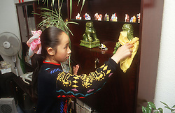 Young girl dusting ornaments and cabinet shelves,