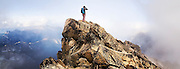 Climber Obadiah Reid stands on the summit of Mount Stuart after a successful ascent by the West Ridge, Alpine Lakes Wilderness, Washington. Mount Stuart is the highest summit of the Stuart Range and the second highest non-volcanic peak in the state.