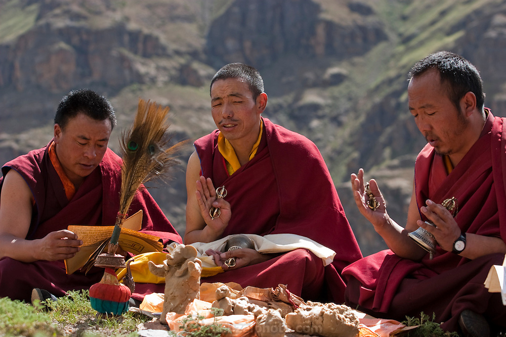 Three monks chant and read holy Buddhist scripts outside their monastery in the Tibetan Plateau. (From the book What I Eat: Around the World in 80 Diets.) The sculpted figurines, called tormas, are offerings made of tsampa (barley flour) and butter.