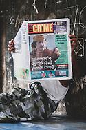 Yangon, Myanmar - October 23, 2011: A Burmese man in Yangon reads a local paper featuring Libyan leader Muammar Gaddafi, who had been killed several days earlier in Libya.