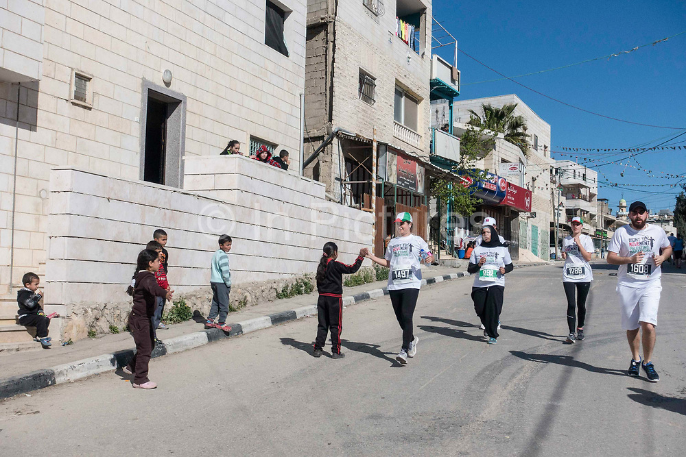 Encouraged by cheering locals, men and women run through the Al Khadr district of Bethlehem on 1st April 2016 in Bethlehem, West Bank. During the Palestine Marathon, thousands of runners, both professional and amateur come from across the globe to take part in the Right to Movement event.