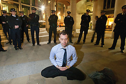 © licensed to London News Pictures. London, UK 01/05/2012. A protester meditating while he is surrounded by police officers at Paternoster Square as Occupy London activists occupy parts of the London Stock Exchange and Paternoster Square as part of May Day protests in London. Photo credit: Tolga Akmen/LNP