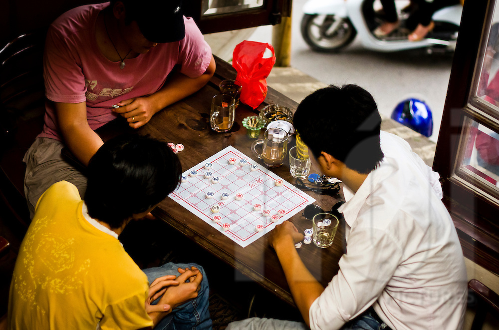 Men play chinese chess at Cafe Xe Co in Hanoi, Vietnam, Asia