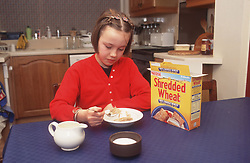 Young girl sitting at table in kitchen eating breakfast,