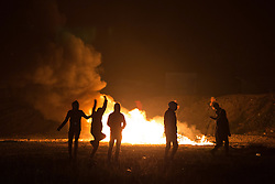 "© Licensed to London News Pictures . 23/10/2016 . Calais , France . Residents set fires at the Calais migrant camp known as "" The Jungle "" , in Northern France , on the evening before the start of the eviction and destruction of the camp . Photo credit: Joel Goodman/LNP"