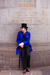 LONDON, UK  29/04/2011. The Royal Wedding of HRH Prince William to Kate Middleton. A spectator in fancy dress takes a break under a statue of Boadicea on Westminster Bridge. Photo credit should read CLIFF HIDE/LNP. Please see special instructions. © under license to London News Pictures