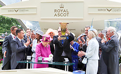 Queen Elizabeth the II presents the trophy for the Diamond Jubilee Stakes to winnning connections of The Tin Man during day five of Royal Ascot at Ascot Racecourse.
