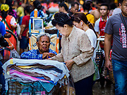 "04 DECEMBER 2018 - BANGKOK, THAILAND:  A woman selling towels in Khlong Toei market. Khlong Toey (also called Khlong Toei) Market is one of the largest ""wet markets"" in Thailand. The market is located in the midst of one of Bangkok's largest slum areas and close to the city's original deep water port. Thousands of people live in the neighboring slum area. Thousands more shop in the sprawling market for fresh fruits and vegetables as well meat, fish and poultry.     PHOTO BY JACK KURTZ"