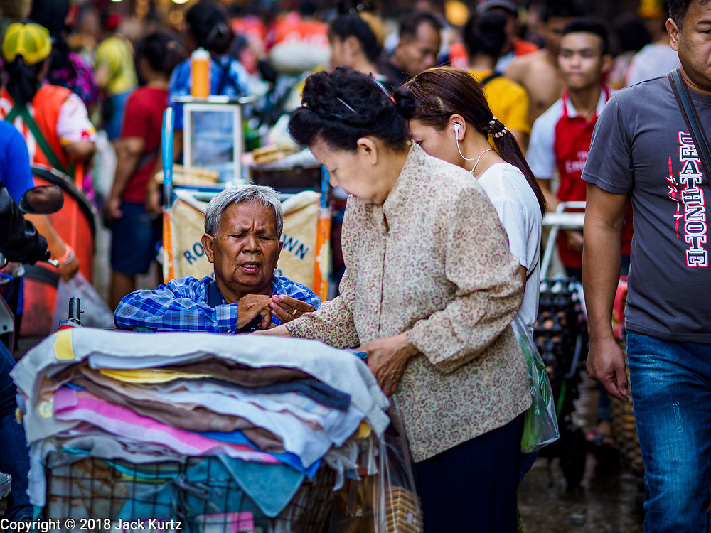"""04 DECEMBER 2018 - BANGKOK, THAILAND:  A woman selling towels in Khlong Toei market. Khlong Toey (also called Khlong Toei) Market is one of the largest """"wet markets"""" in Thailand. The market is located in the midst of one of Bangkok's largest slum areas and close to the city's original deep water port. Thousands of people live in the neighboring slum area. Thousands more shop in the sprawling market for fresh fruits and vegetables as well meat, fish and poultry.     PHOTO BY JACK KURTZ"""